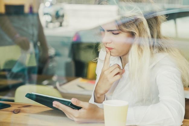 Pensativo profesional femenino sentado en el escritorio en el espacio de trabajo conjunto o cafetería, usando tableta