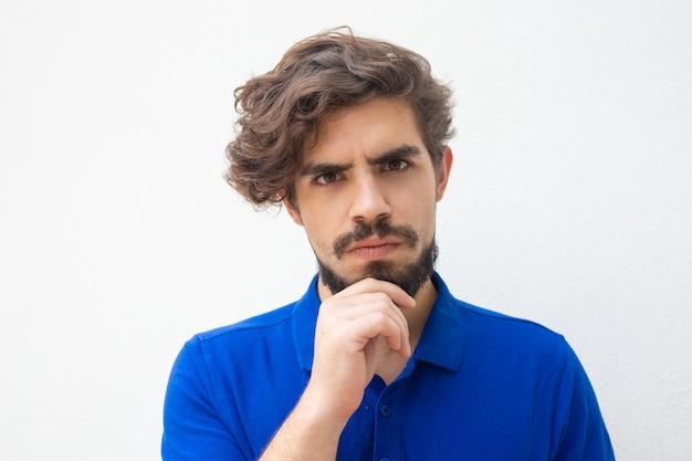 Pensativo serio chico de pelo rizado tocando la barbilla