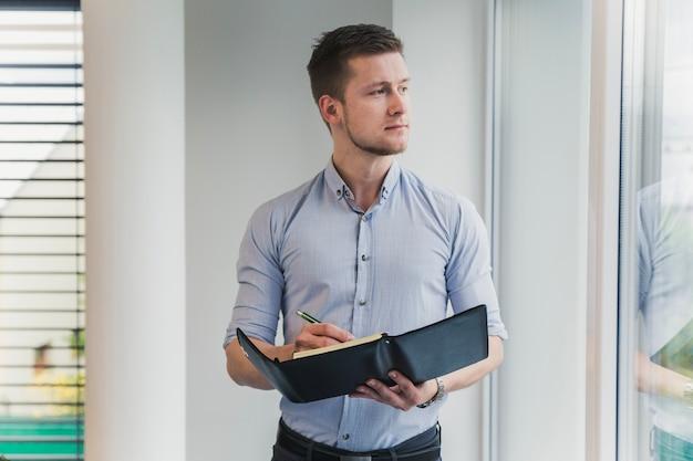 Pensativo trabajador posando con el bloc de notas