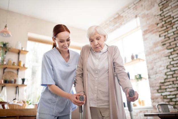 Pensionista caminando con muletas de pie cerca del cuidador