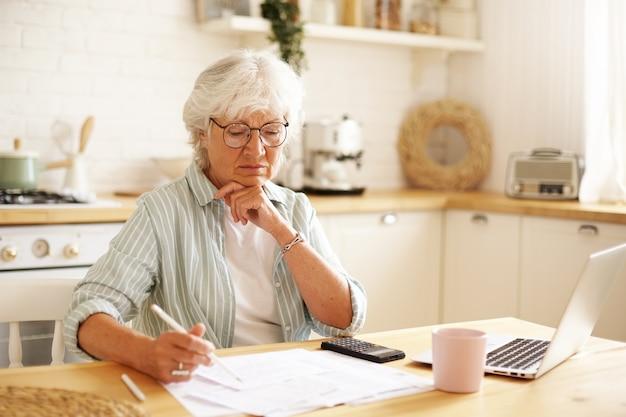 Pensionista concentrada usando anteojos enfocados en papeles financieros mientras paga facturas en línea usando laptop, sosteniendo lápiz, tomando notas. personas, tecnología, finanzas y presupuesto nacional