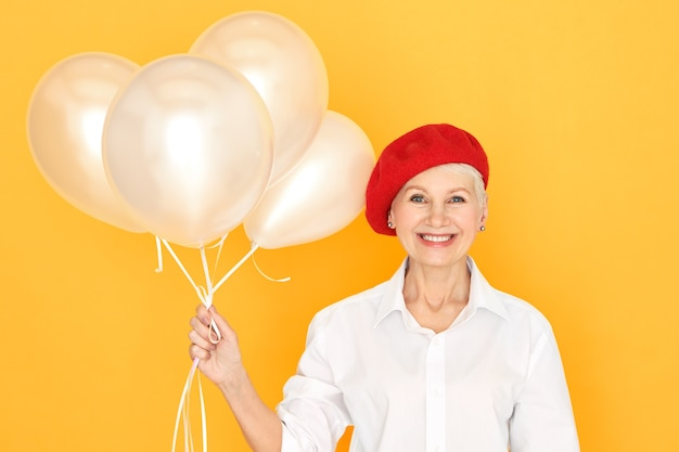 Pensionista europea alegre de moda con camisa blanca y gorro rojo sosteniendo globos de helio y sonriendo, celebrando aniversario o cumpleaños, con expresión facial feliz y llena de alegría