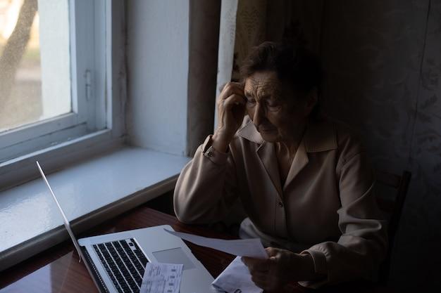 Pensionista lee innumerables trabajos y está muy concentrado. mujer mayor cálculo de impuestos en casa. mujer jubilada calculando sus facturas domésticas. concepto de negocio, ahorros, seguro de anualidad, edad y personas