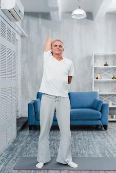 Pensionista masculino sonriente que hace estirando ejercicio delante del sofá en casa