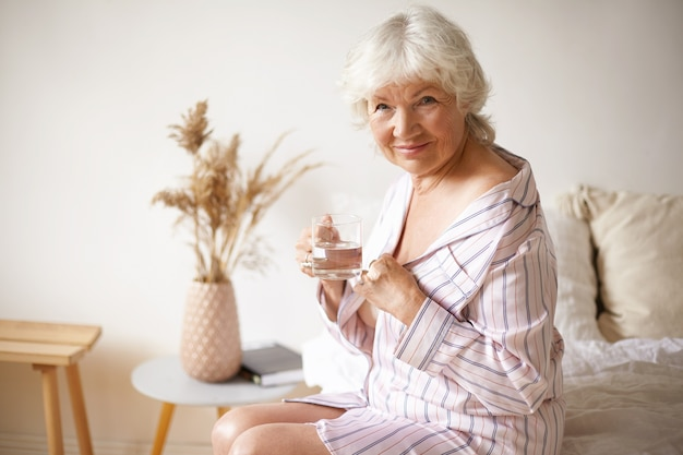 Pensionista de mujer europea de pelo gris feliz soñoliento en elegante vestido de noche a rayas sentado en el dormitorio en la cama, mirando, bebiendo agua fresca de vidrio. hábitos saludables, edad y jubilación