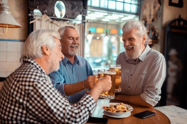 Pensionista positivo. pensionistas envejecidos canosos positivos haciendo sonar sus vasos con cerveza