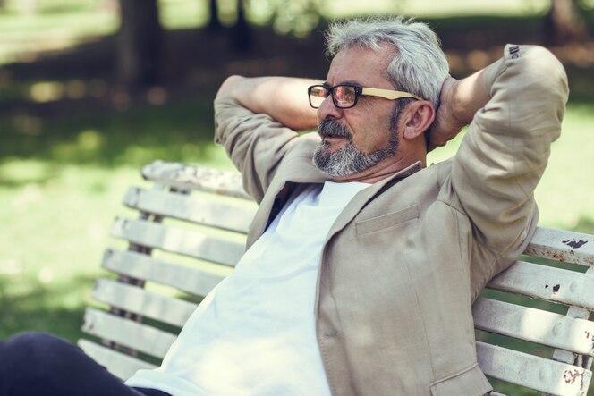 Pensive hombre maduro sentado en el banco en un parque urbano.