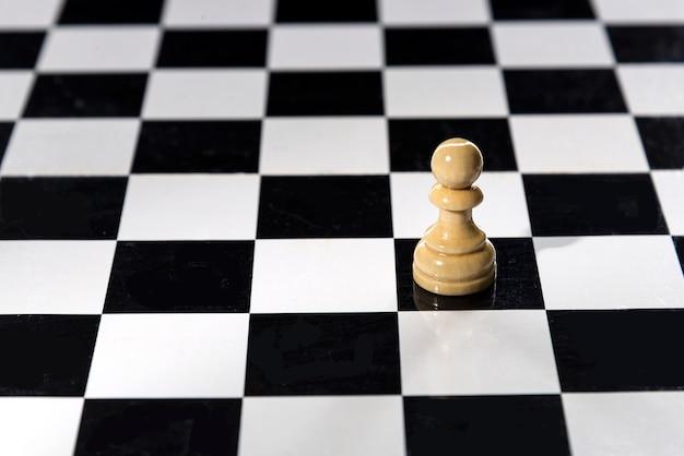 Peón de ajedrez blanco independiente en una mesa de ajedrez