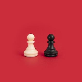 Un peón de ajedrez blanco y negro sobre un fondo rojo brillante, perfecto para conceptos de diversidad