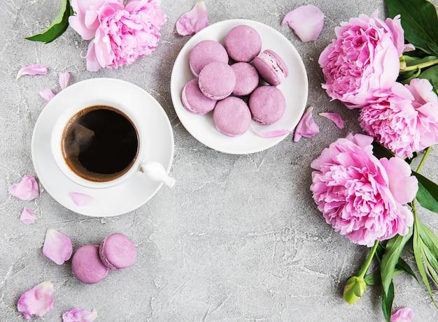Peonía rosa con café y macarons.