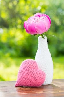 Peonía rosa en un jarrón blanco decorado con tejido de punto y un corazón de punto rosa sobre una mesa de madera