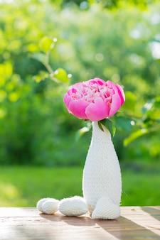 Peonía rosa en un jarrón blanco decorado con tejido de punto y tres corazones de punto blanco sobre una mesa de madera