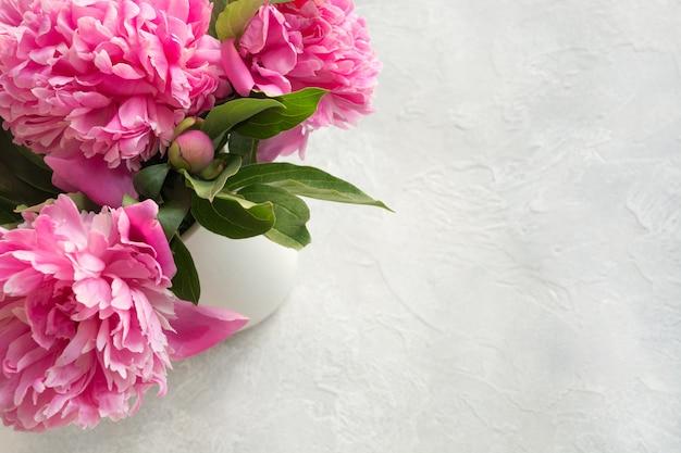 La peonía rosada florece en florero en gris. vista superior.