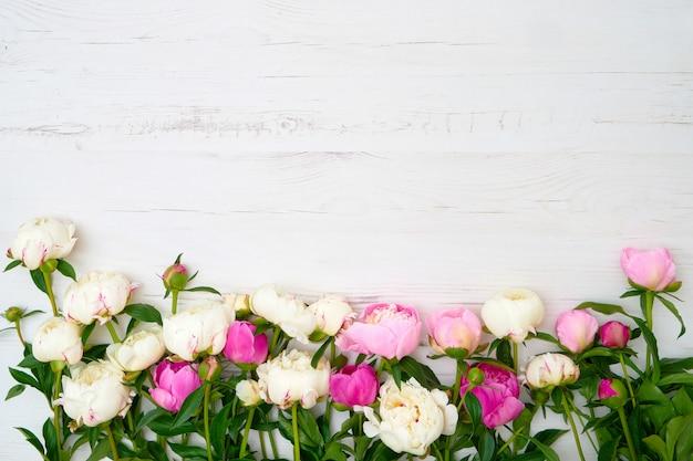 Peonías blancas y rosadas en mesa de madera blanca.