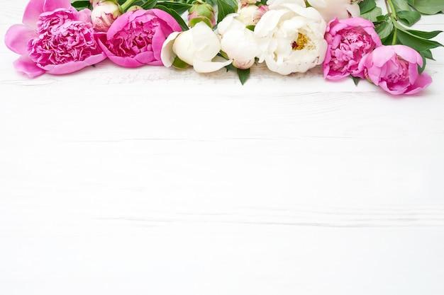Peonías blancas y rosadas en la mesa de madera blanca.