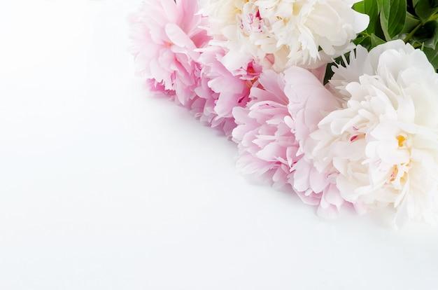 Peonias blancas y rosadas sobre una mesa blanca.
