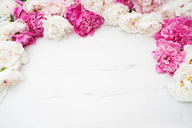Peonías blancas y rosas en madera blanca.