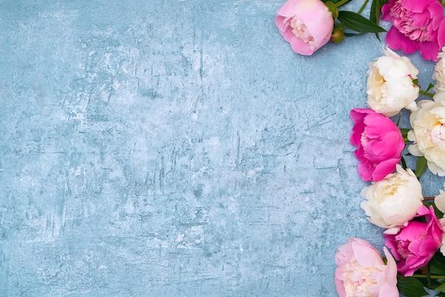 Peonías blancas y rosas sobre azul.