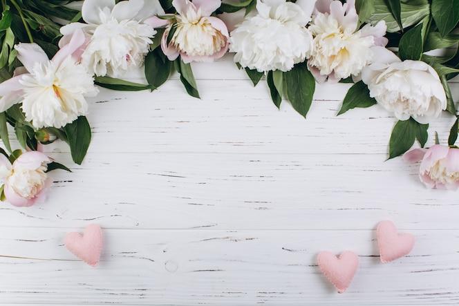 Peonías blancas y corazones de color rosa sobre un fondo de madera. copie el espacio y ponga plano.