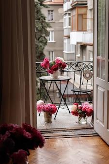 Peonías en jarrones en el balcón del apartamento de la ciudad