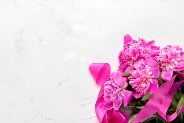 Peonías rosas y cinta rosa sobre una piedra clara