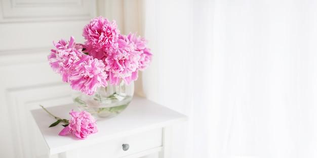 Peonías rosas en florero de vidrio. flores en la mesa blanca cerca de la ventana. luz de la mañana en la habitación. hermosa flor de peonía para catálogo o tienda en línea. tienda de flores y concepto de entrega. bandera. copia espacio