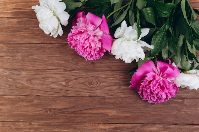 Peonías rosas y blancas sobre un fondo de madera