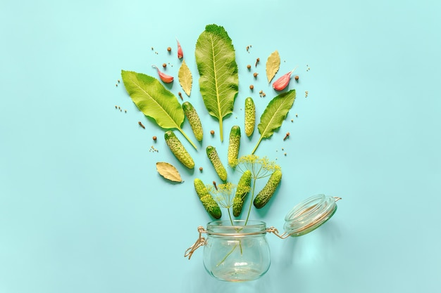 Pepinillos en vinagre. ingredientes para pepinillos marinados y frasco de vidrio sobre fondo azul. receta culinaria conceptual