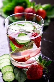 Pepino y agua de desintoxicación de fresa en vidrio sobre superficie negra,