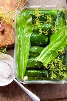 Pepinos frescos con hierbas y especias preparadas para encurtir en recipiente de vidrio