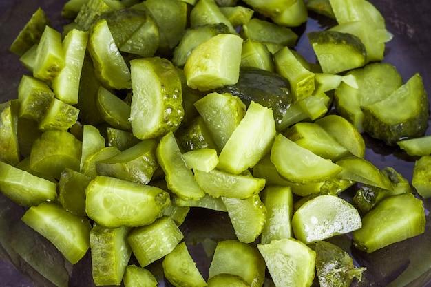 Pepinos o pepinillos en vinagre con un cuchillo en una tabla de cortar de madera. fondo azul gris