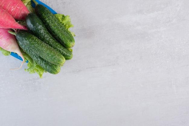 Pepinos sanos y rábanos rojos en placa azul. foto de alta calidad