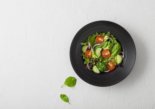 Pepinos y tomates, cebolla morada y espinacas se mezclan en ensalada de verduras frescas en un plato de tazón negro sobre fondo blanco.