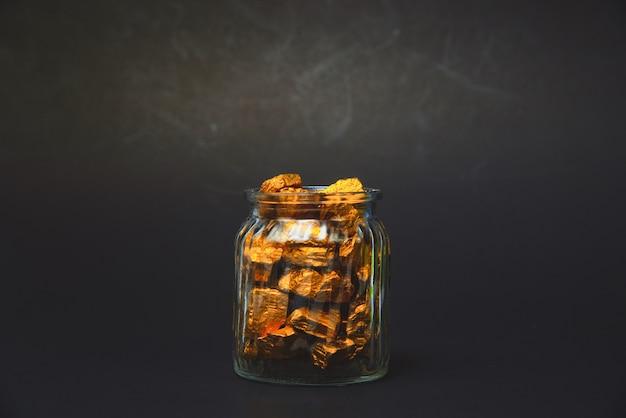 Pepitas de oro, mineral de oro y frasco de vidrio en una habitación oscura.