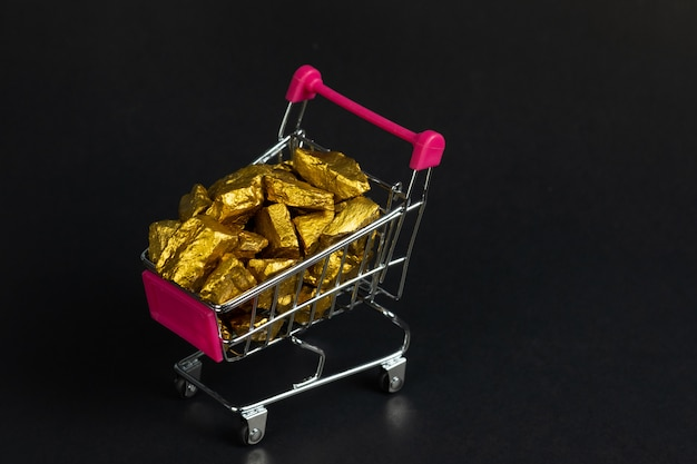 Pepitas de oro o mineral de oro en el carrito de compras o en el carrito de supermercado