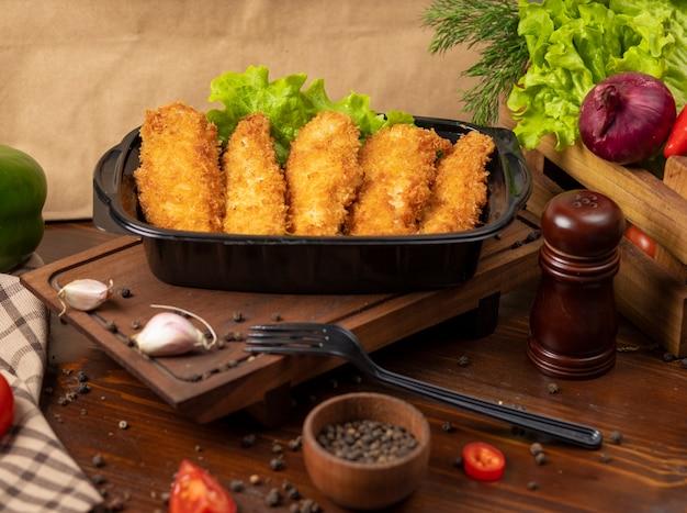 Pepitas de pollo frito estilo kfc para llevar en un recipiente negro
