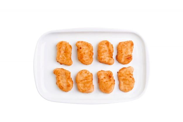 Pepitas de pollo frito en la placa blanca aislada en el fondo blanco. vista superior