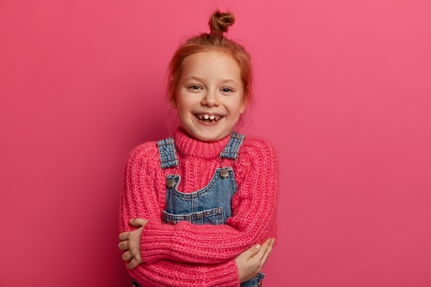 La pequeña y alegre niña pelirroja se abraza, se siente cómoda, tiene un nuevo suéter rosa de lana, un atuendo suave y cálido, sonríe con los dientes, muestra los dientes que le faltan, tiene el pelo pelirrojo, aislado en una pared rosa.