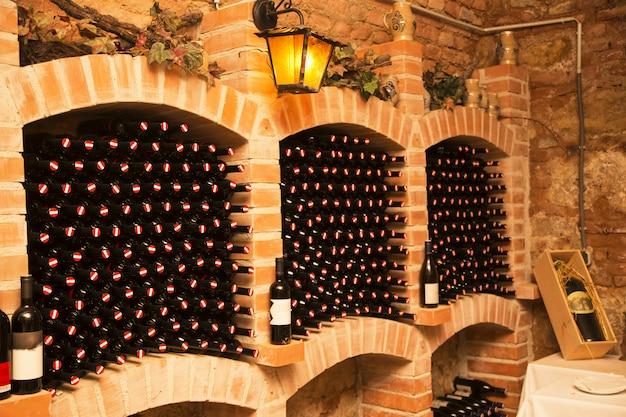 Pequeña y antigua bodega con muchas botellas llenas y barriles.
