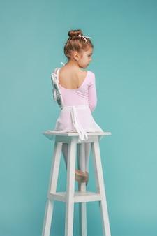 La pequeña bailarina bailarina sobre fondo azul.