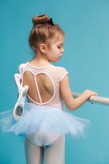 La pequeña bailarina de balerina sobre fondo azul.