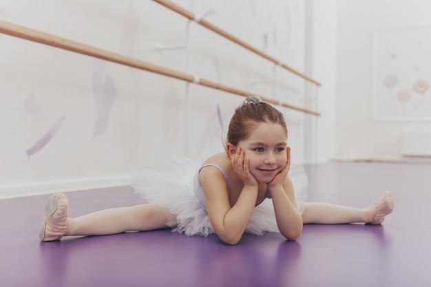 Pequeña bailarina feliz linda que hace fracturas en la escuela de danza.
