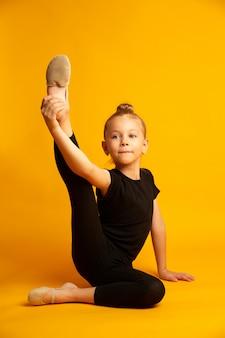 Pequeña bailarina en leotardo estirando las piernas durante el entrenamiento
