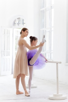 La pequeña bailarina posando en la barra de ballet con maestra personal en estudio de danza