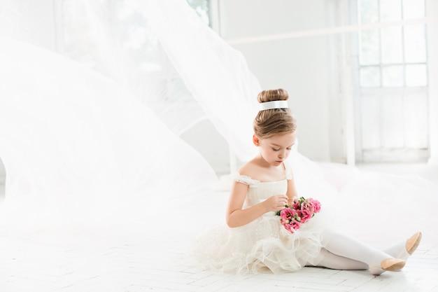 La pequeña bailarina con tutú blanco en clase en la escuela de ballet
