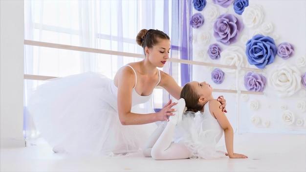 Pequeña bailarina en tutú blanco se estira en pose de rana con maestra de ballet