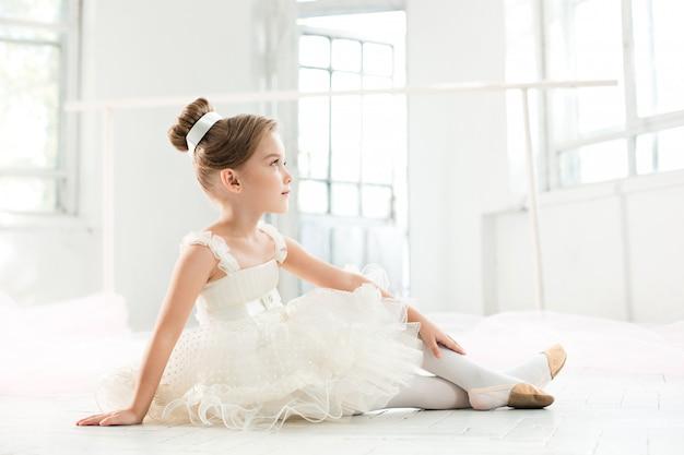 Pequeña balerina en tutú blanco en clase en la escuela de ballet