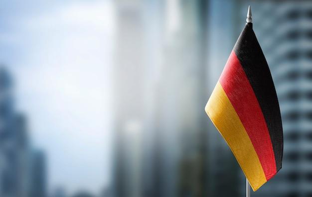 Una pequeña bandera de alemania en la ciudad borrosa