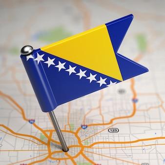 Pequeña bandera de bosnia y herzegovina sobre un fondo de mapa con enfoque selectivo.