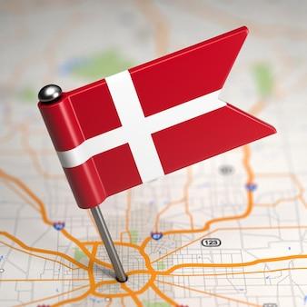 Pequeña bandera de dinamarca sobre un fondo de mapa con enfoque selectivo.